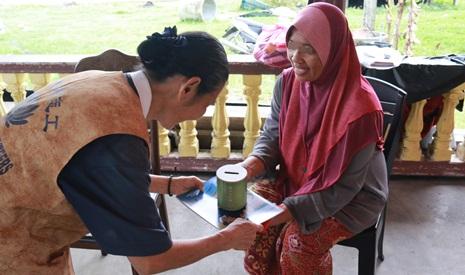 曾吉蘭(慈琅)師姊將竹筒及慈濟月刊送給受災居民,勉勵大家在困難過去後可以一起加入助人的行列,做一個有福的人。【攝影者:尤靜蓓(慮忱)】