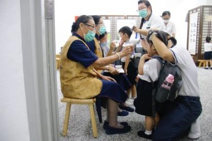 地下停車場入口處設立了健康檢查站,小孩子一進門必須先測量體溫及檢查口腔和手指。【攝影:謝明潔】